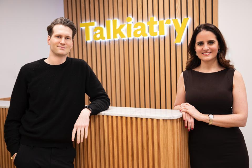 Robert Krayn and Georgia Gaveras, cofounders of Talkiatry, stand in front of a yellow Talkiatry sign