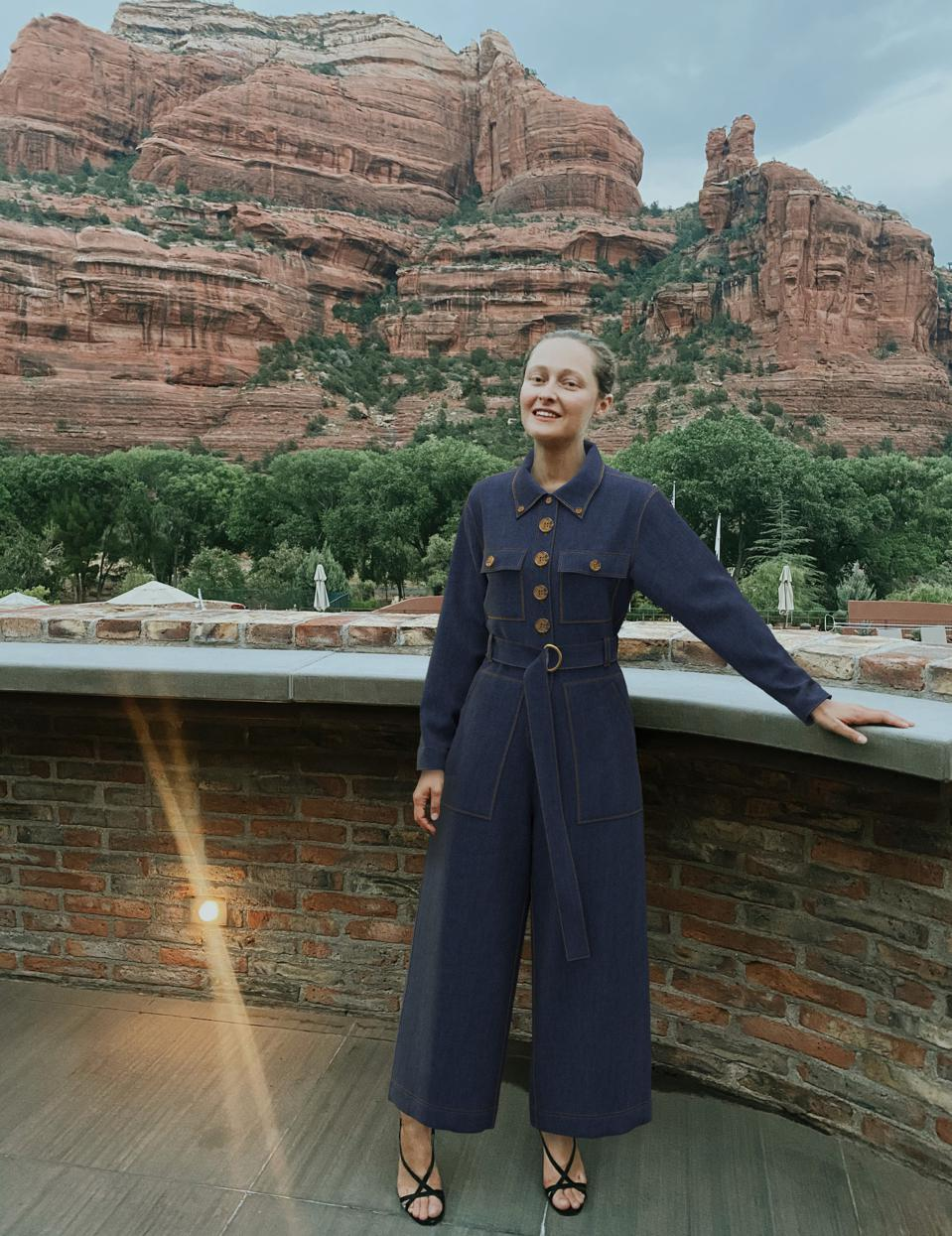 Daria Shapovalova wearing a virtual fashion outfit by The Fabricant in front of mountains