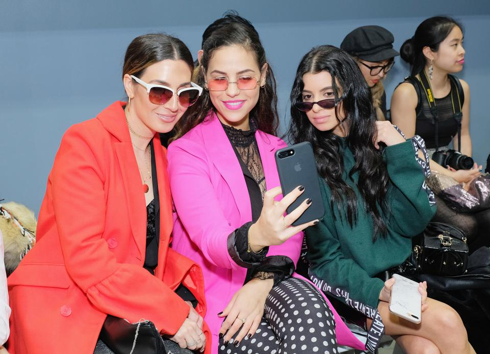 influencers taking selfies, front row at fashion week
