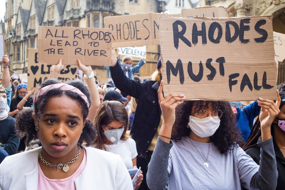 A woman wearing a facemask is seen displaying a placard...