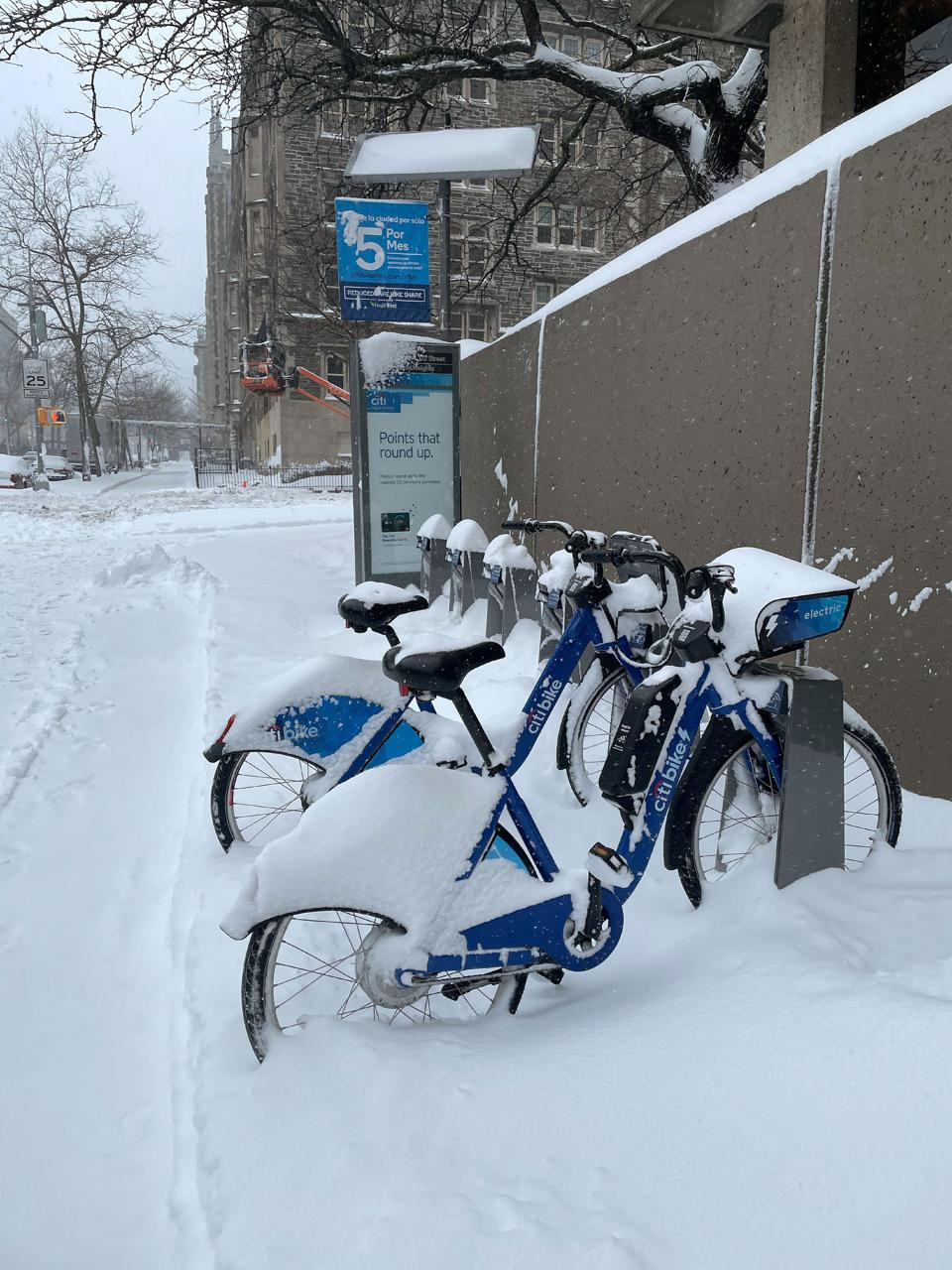 Electric city bikes on a stand in snow on the Upper West Side, New York.