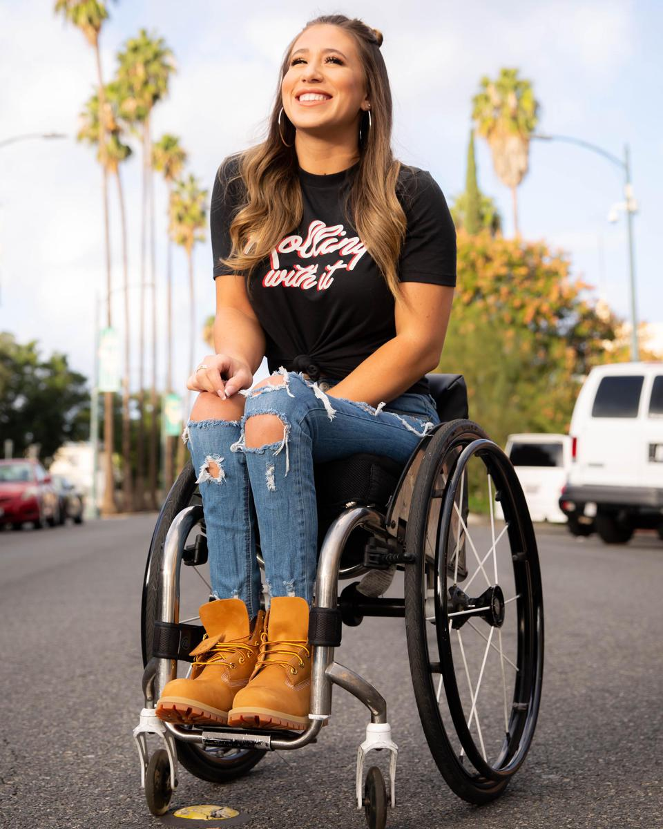 Chelsie Hill smiles in a wheelchair on a sunny street.