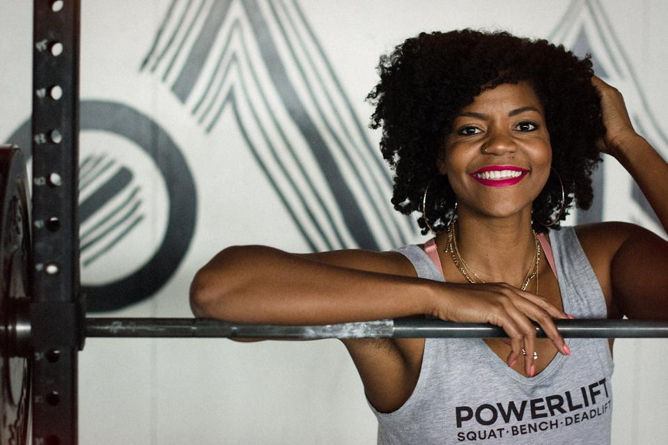 Fitness trainer Chrissy King smiles in a gym.