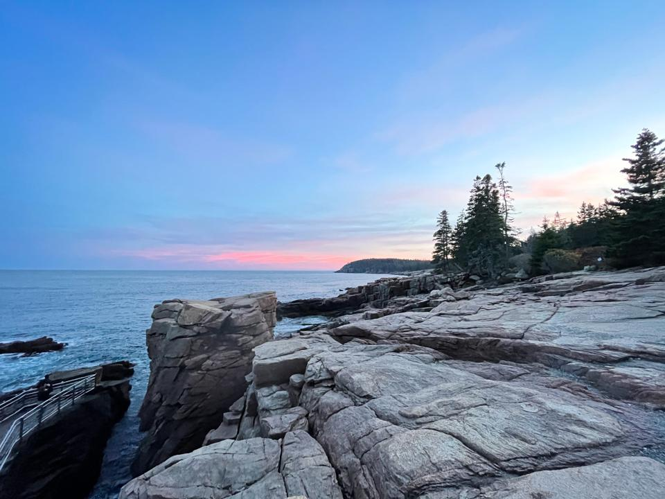The sun is setting over the rocks and sea at Acadia National Park in Maine