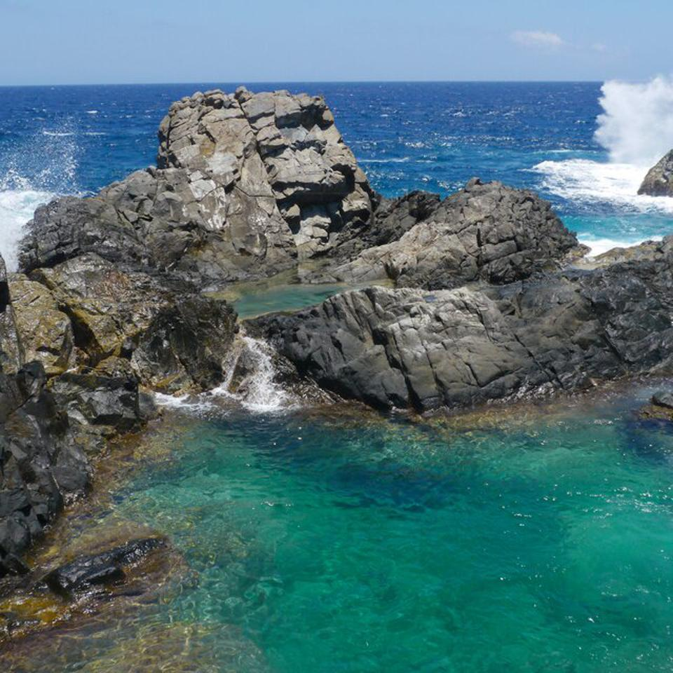 The rocks and ocean form a natural pool in Aruba.