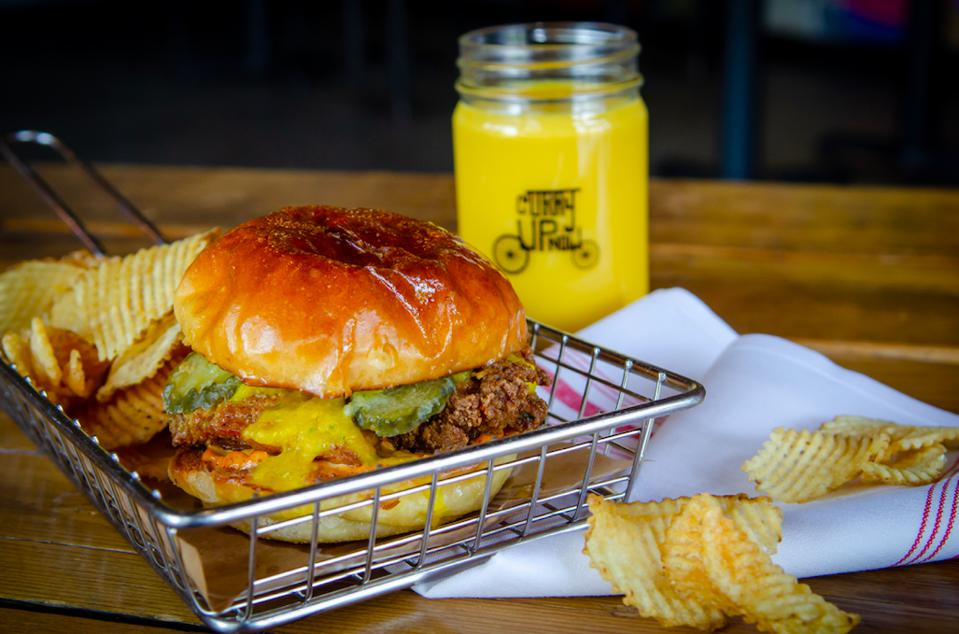 Fried Chicken Sandwich garnished with sauce and pickles from Curry Up Now with a side of chips and a drink