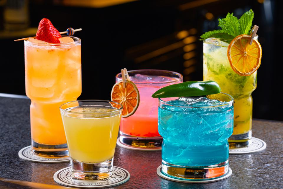 Five colorful cocktails with garnish on a bar sitting on coasters