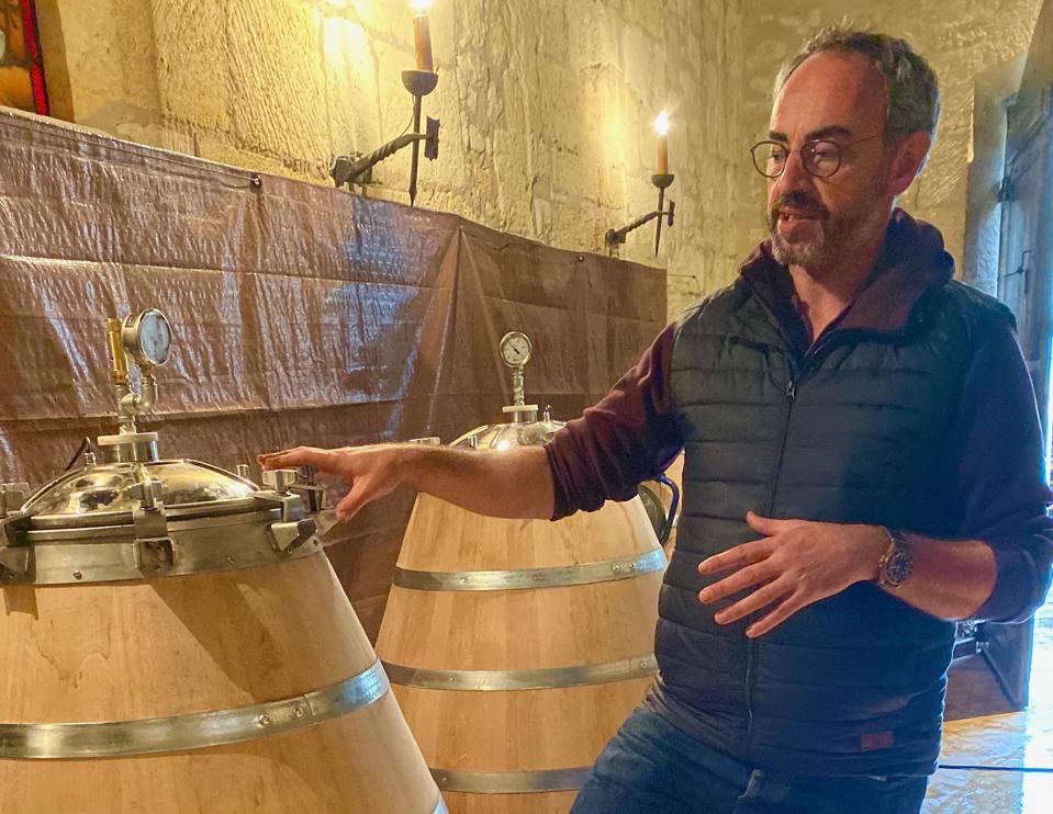 Winemaker next to wooden barrels