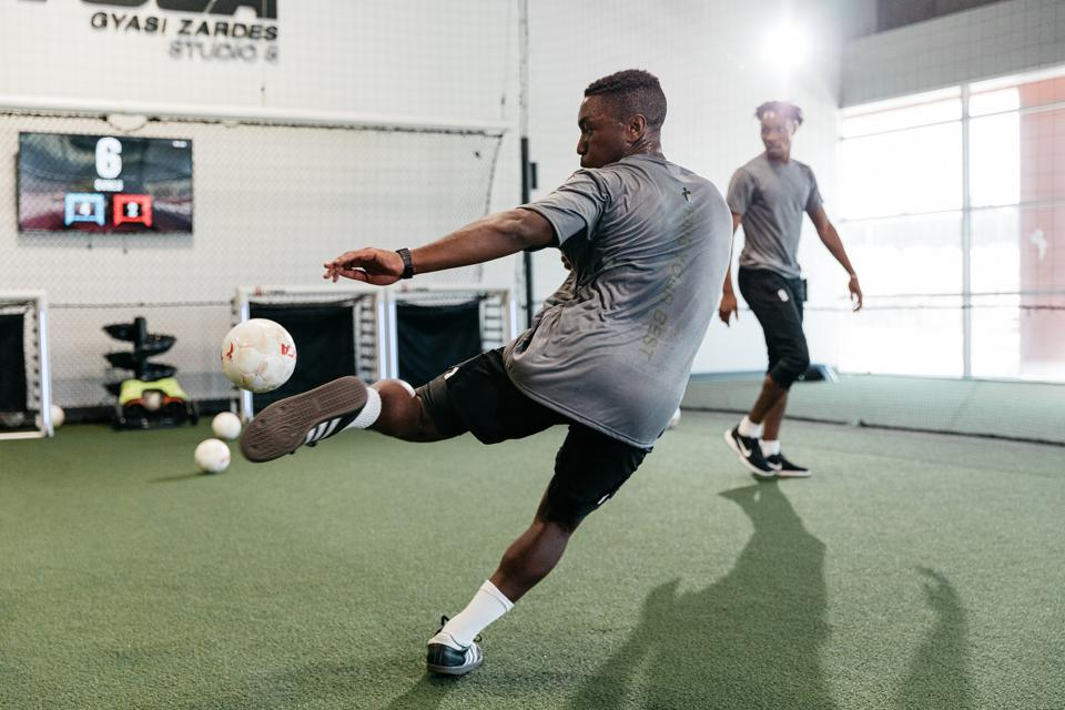 Image of person striking a football at a TOCA Sport training center.