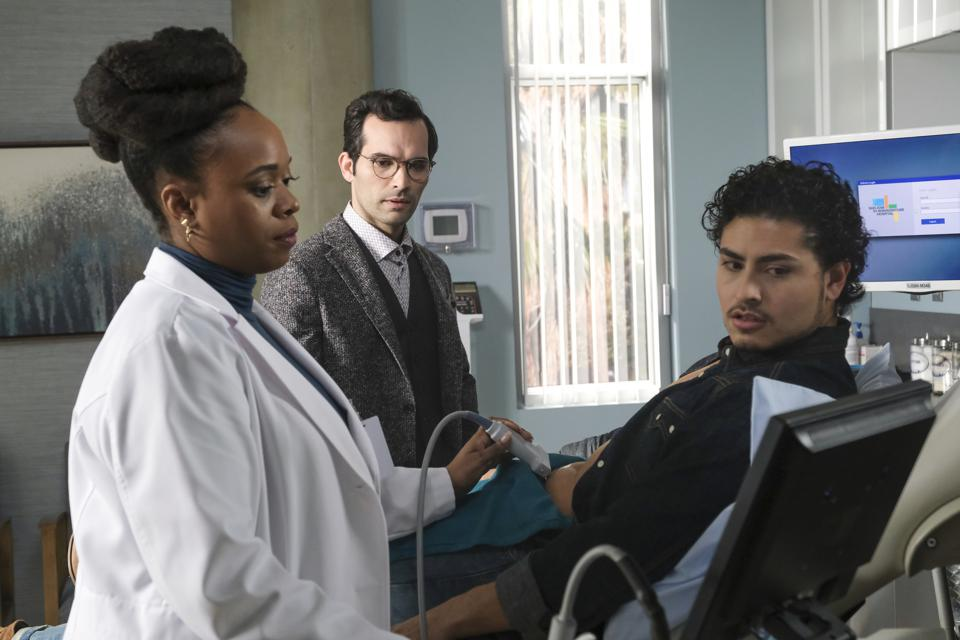 A doctor performs an ultrasound on a pregnant transgender man as his husband watches.
