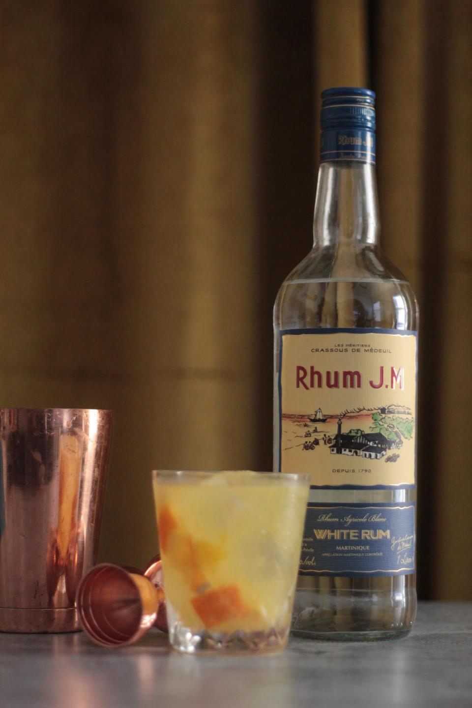 Bottle of Rhum J.M. next to Lucky Louis cocktail
