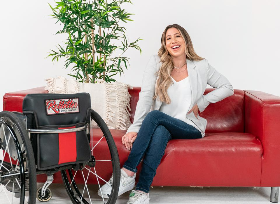 Chelsie Hill sits on a red couch smiling next to a Rollettes wheelchair.