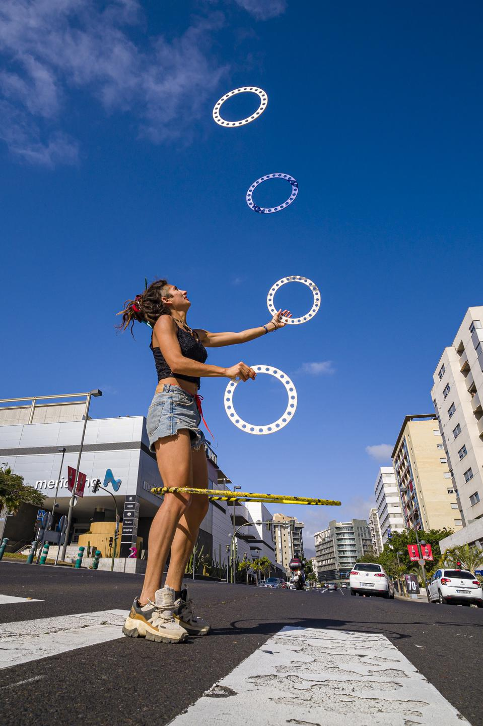 A young woman is juggling with 4 discs on a road crossing...