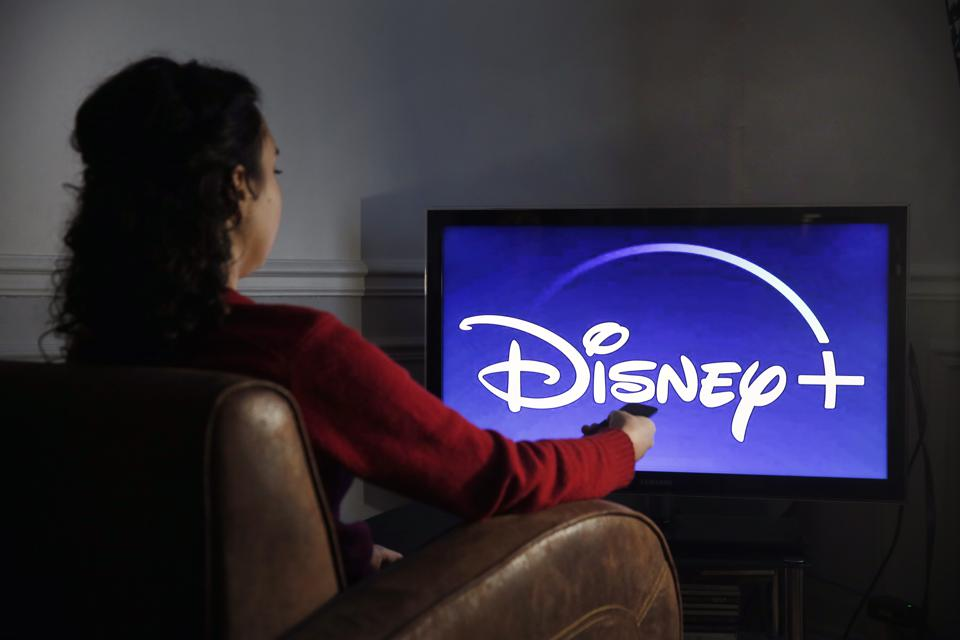 Photo of a woman getting ready to watch a movie on Disney+