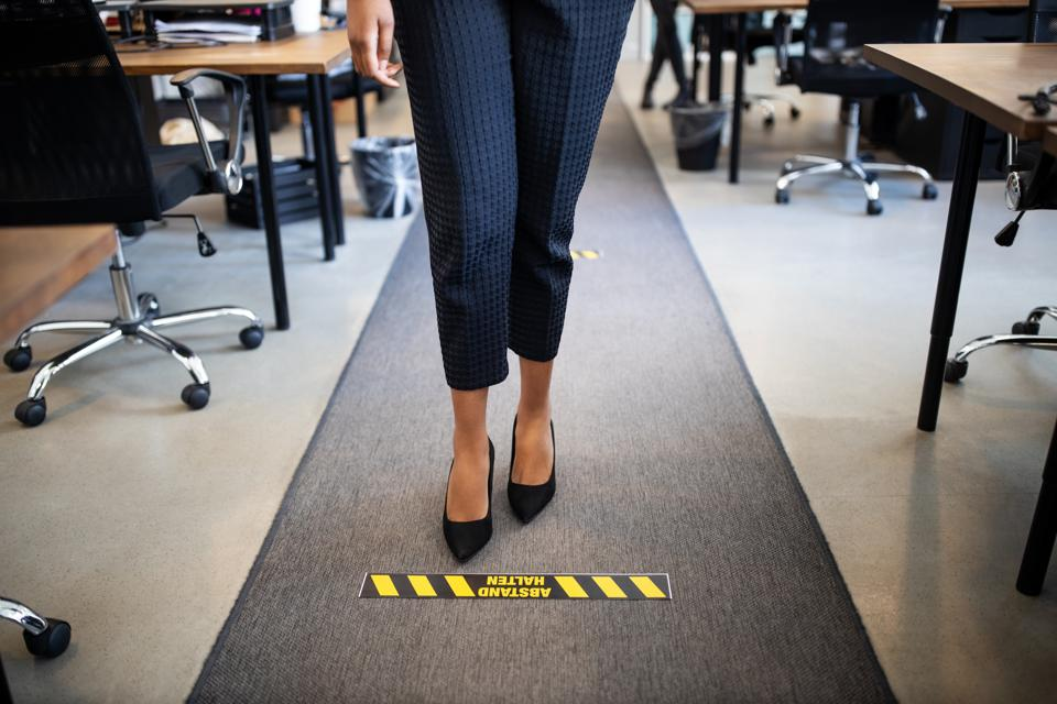 Businesswoman standing behind social distancing signage on floor