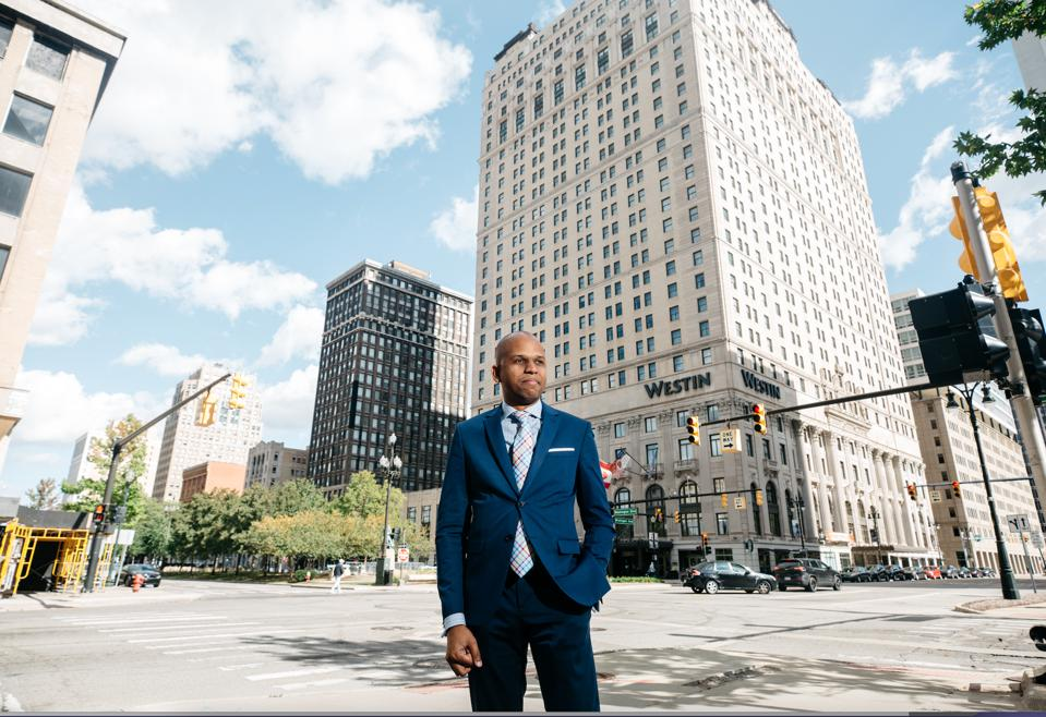 Ricardo Pagan stands in front of a Westin Hotel in Detroit.