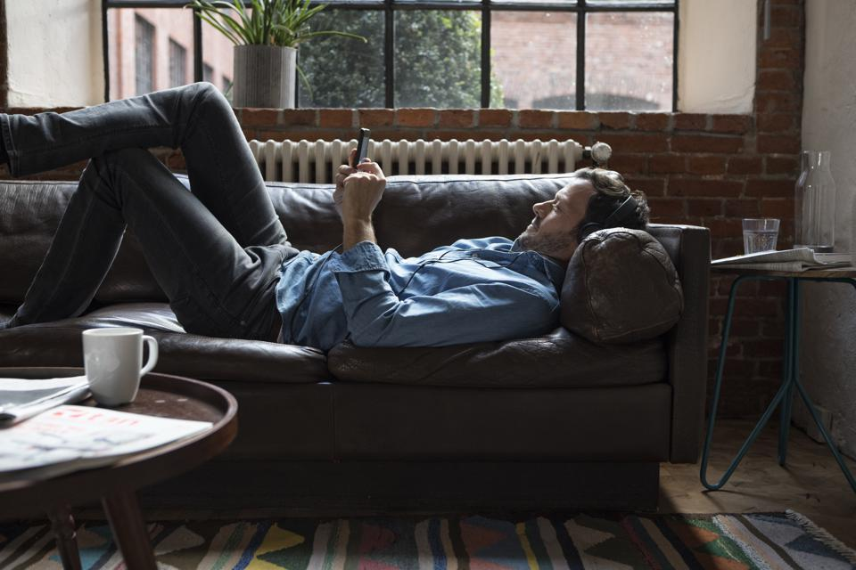 Man lying on couch, using smart phone