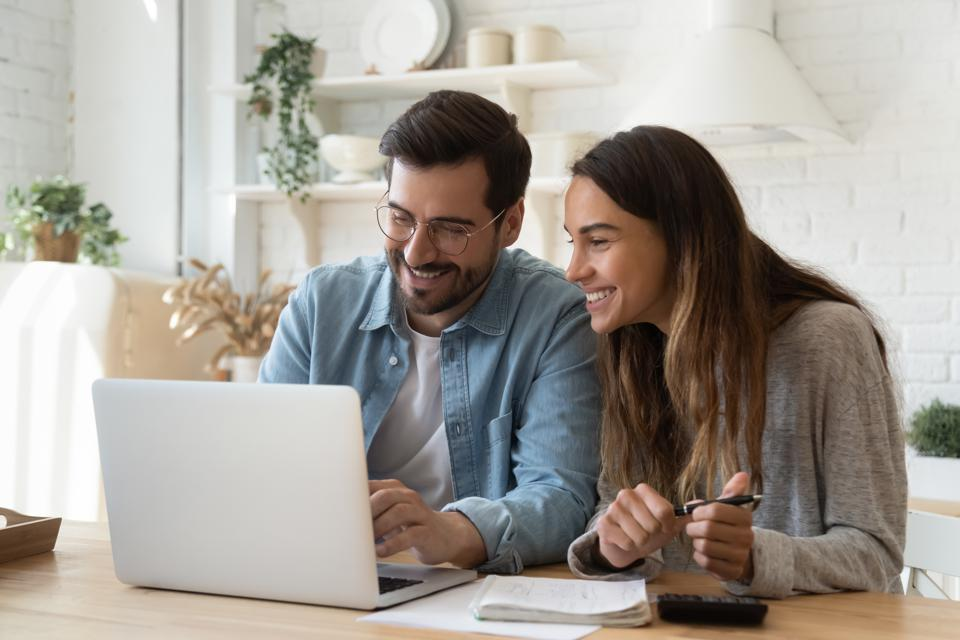 Happy young couple paying bills online in computer app