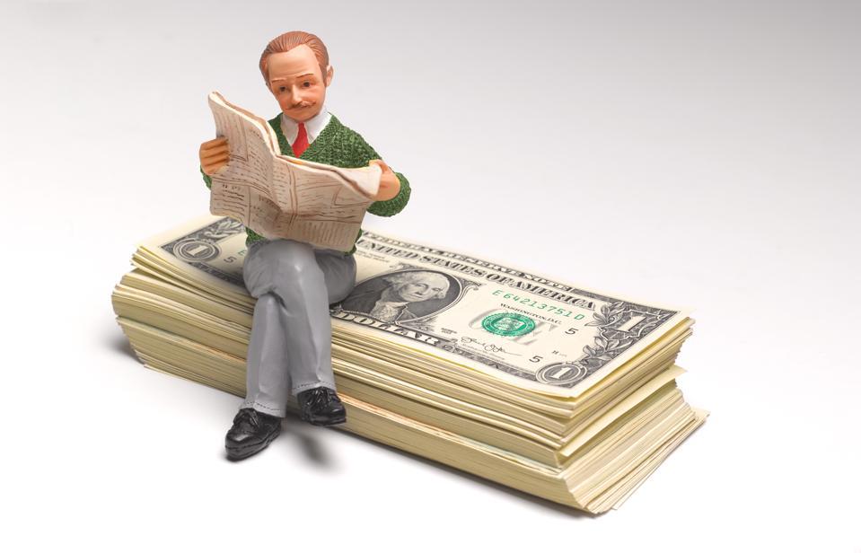Pensioner sitting on stack of US Dollars