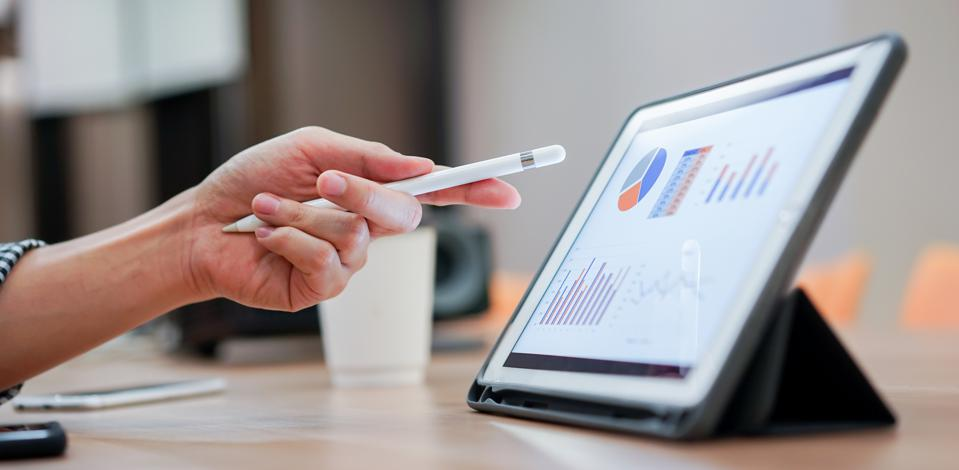 Close up of financial professional's hand using  a stylus pen to point to a tablet with financial data