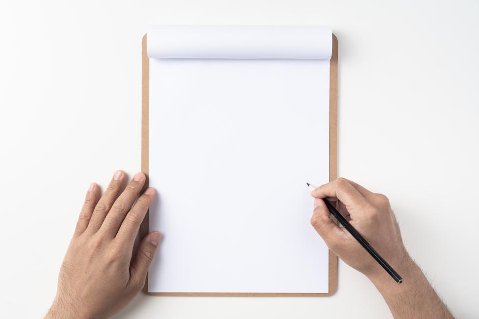 Cropped Hands Of Man Writing On Paper Against White Background