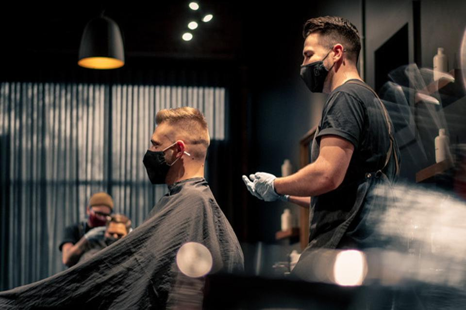 A barber and their client, both wearing masks, at Curriculum USA.