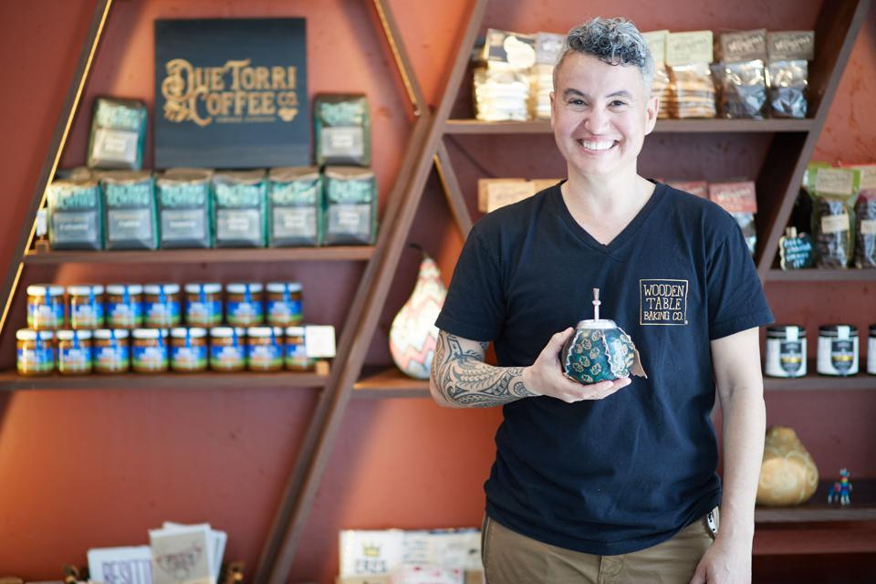 The founder of Wooden Table Baking Co holding a yerba mate