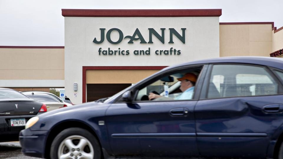 A car in front of a Joann crafts store.