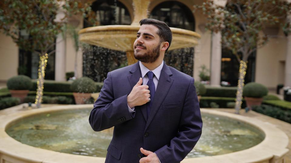 Young man in a suit standing in front of a fountain