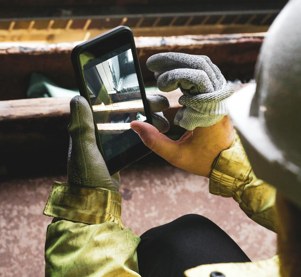 An architect holding a smartphone on a construction site.