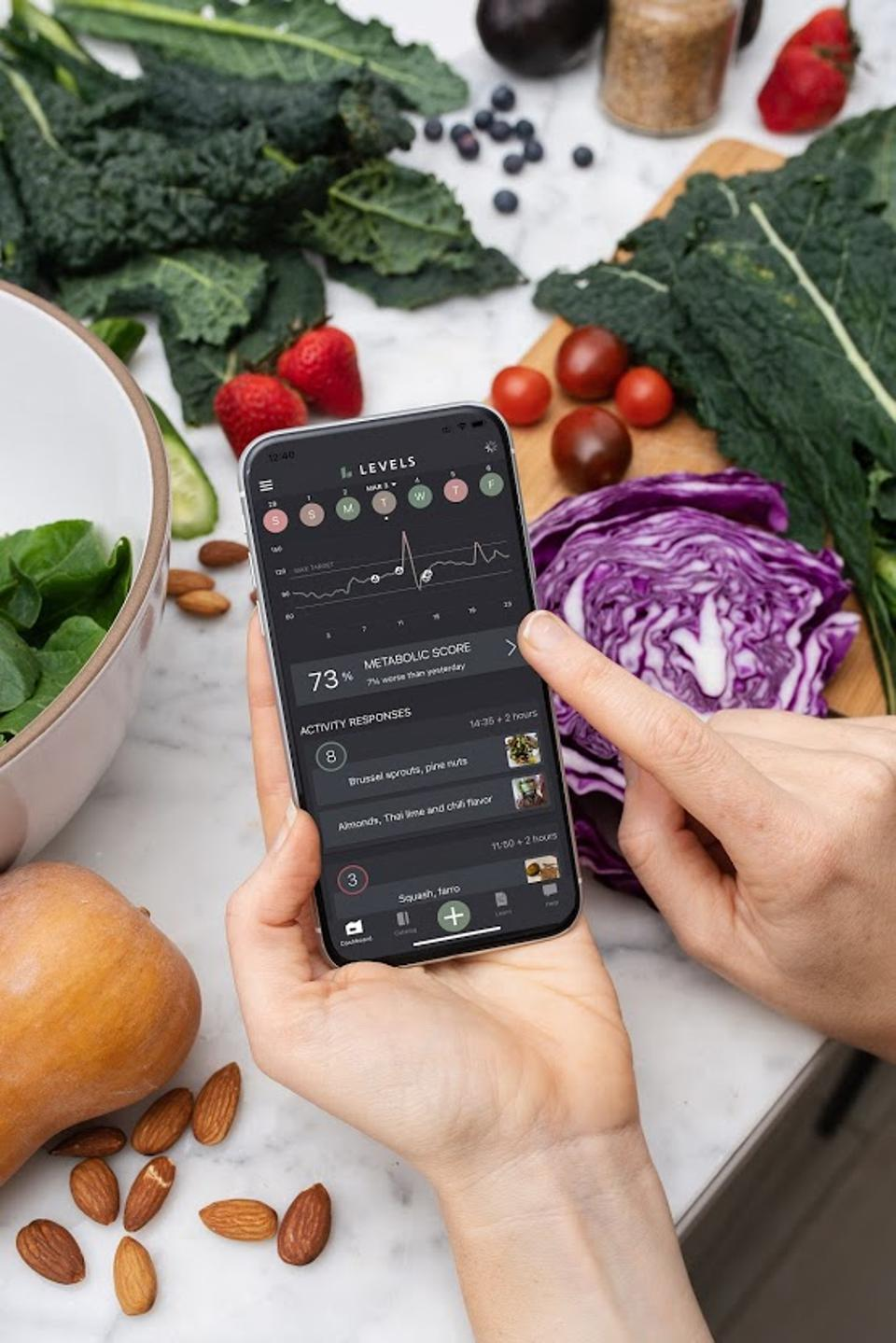 A hand holding a phone which shows a blood sugar graph over a table of healthy foods