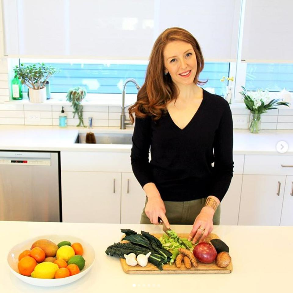 A white woman wearing a black sweater chopping vegetables and smiling at camera