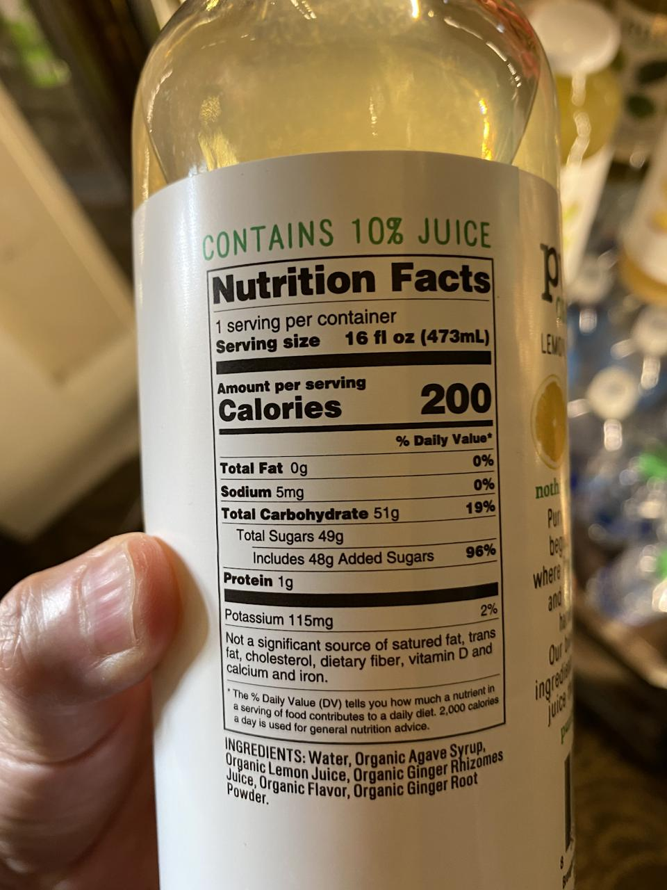 A hand holding a bottle showing the nutritional information on a juice drink.