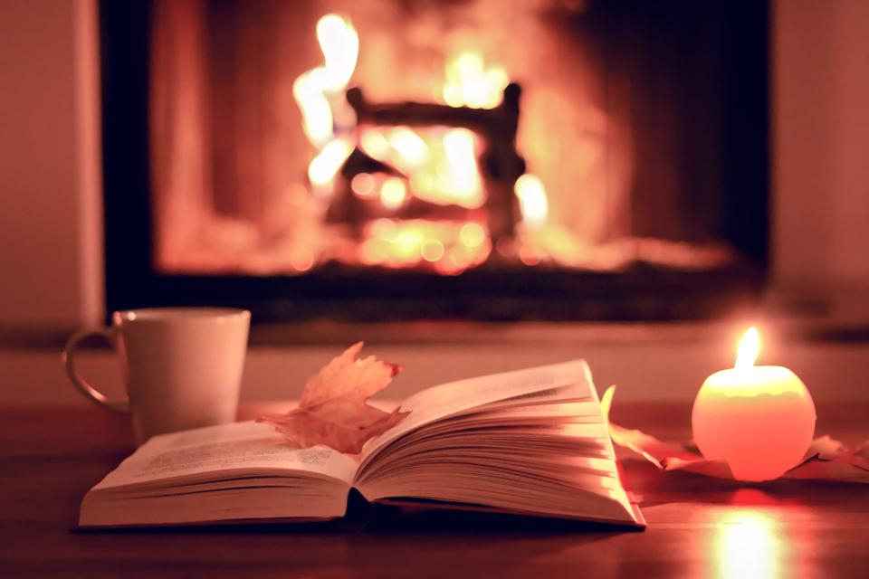 Cozy evening with fireplace at home. Close up photo of open book with leaf, cup of tea and candle with fire at background.