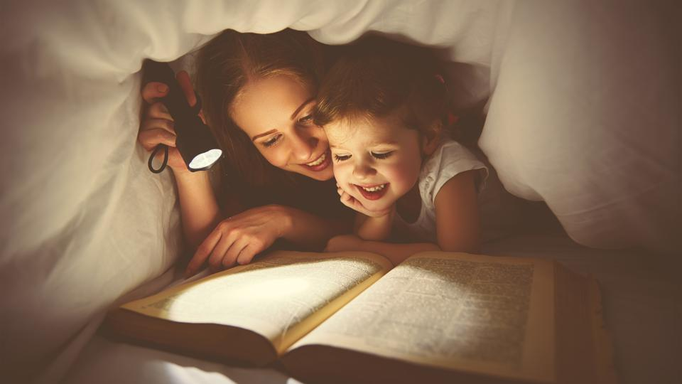 Family reading bedtime. Mom and child reading book