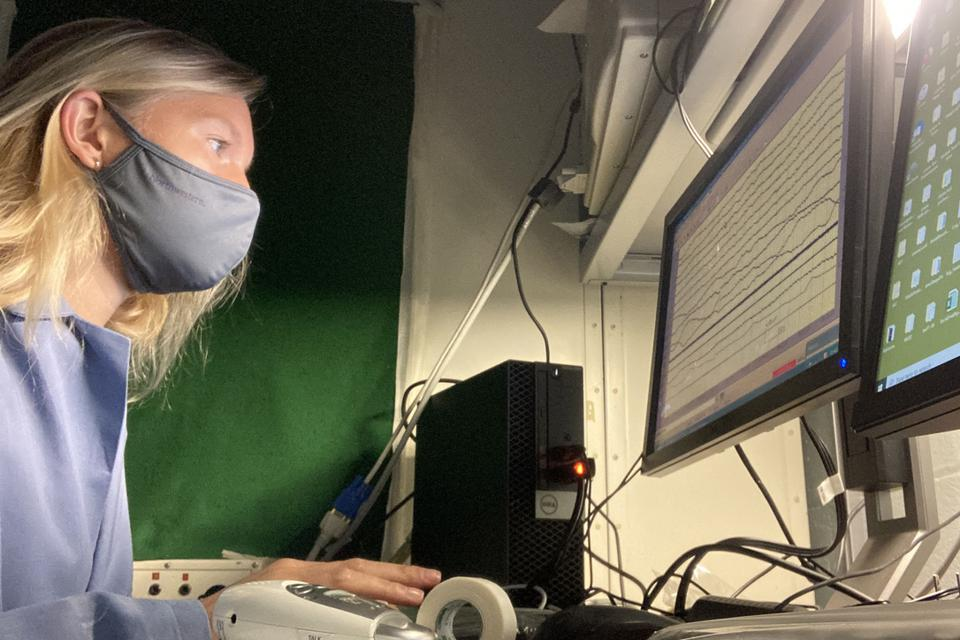 Konkoly watches brain signals from a sleeping participant in the lab.