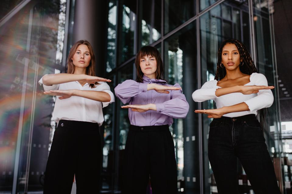 Portrait Of Women Gesturing Equal Sign While Standing Against Building