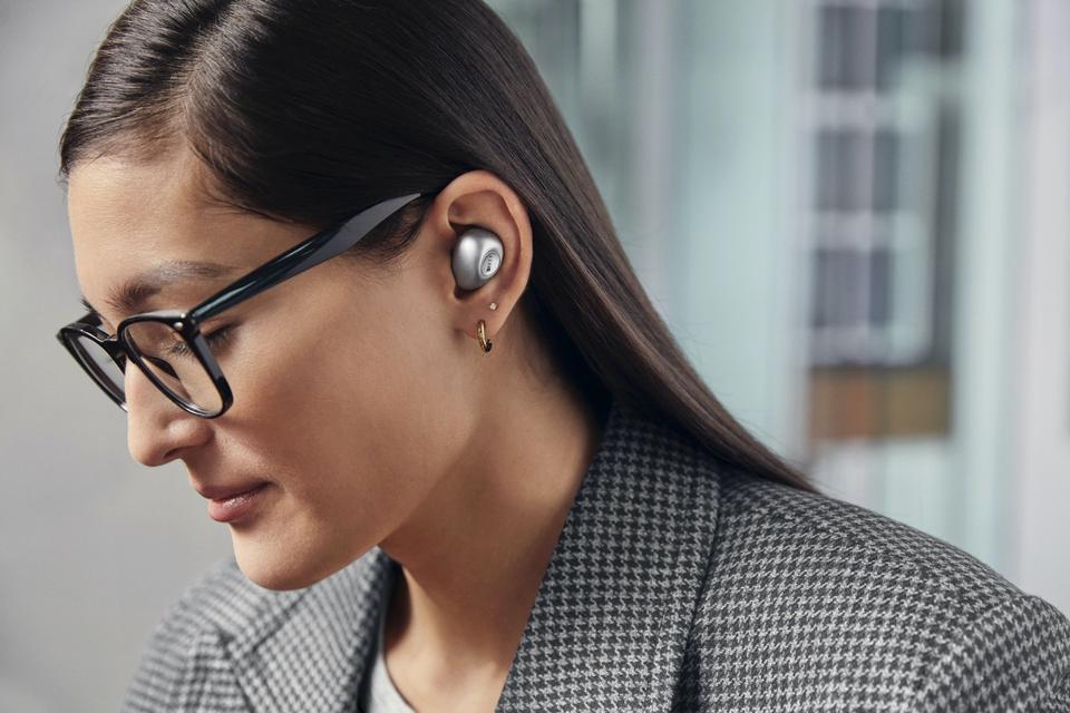 Woman wearing pair of KEF Mu3 earphones