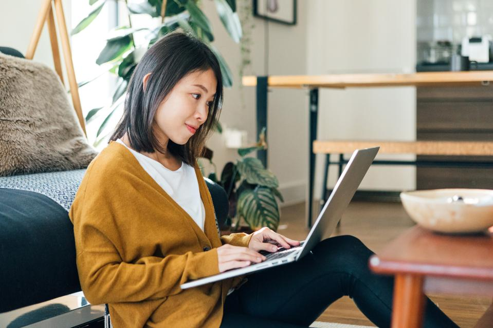 Young woman on a video conference using laptop working at home