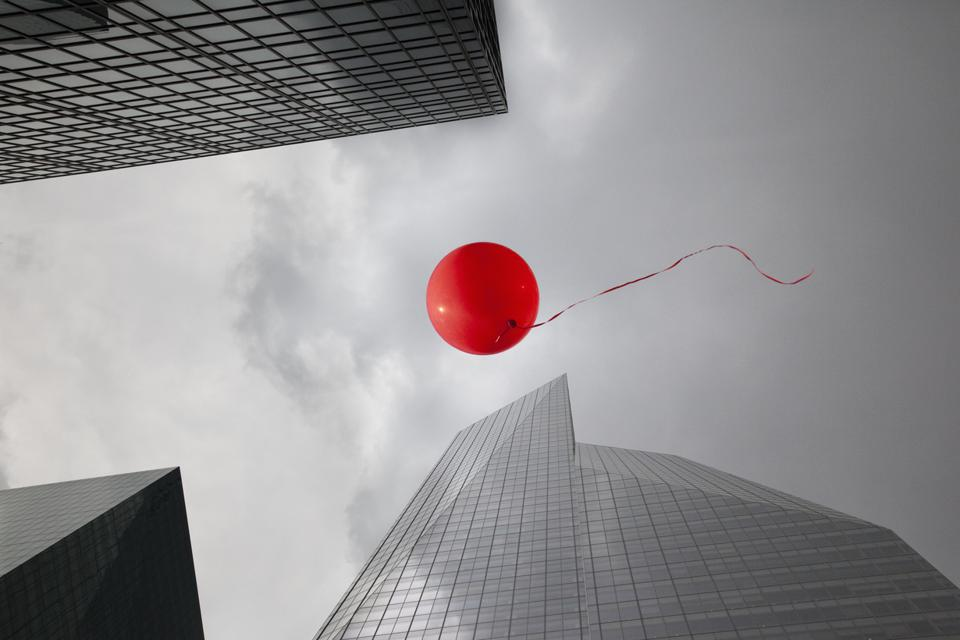 Red balloon floating through skyscrapers