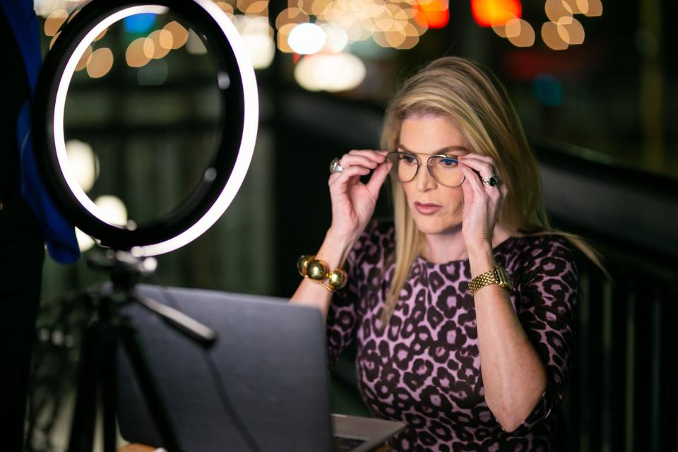 Ana Cruz sitting at computer adjusting her glasses