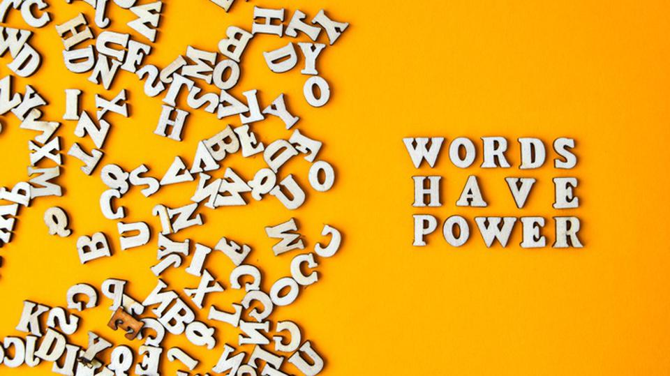 Quote WORDS HAVE POWER made out of wooden letters on bright yellow background.