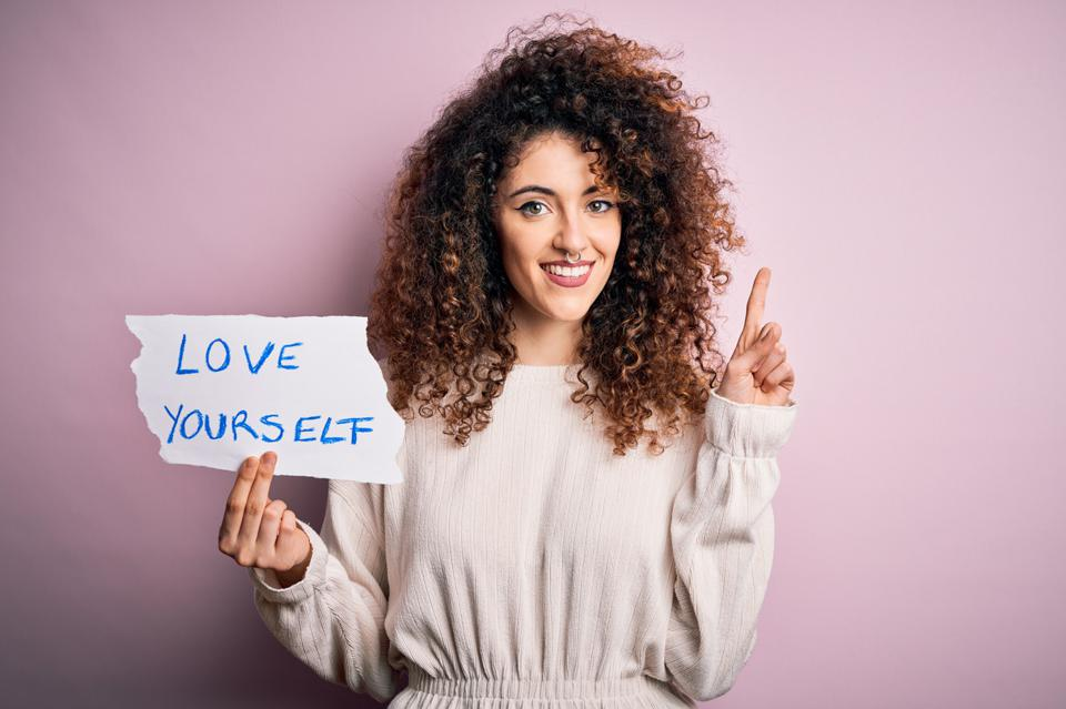 Young beautiful woman with curly hair and piercing holding paper with love yourself message surprised with an idea or question pointing finger with happy face, number one