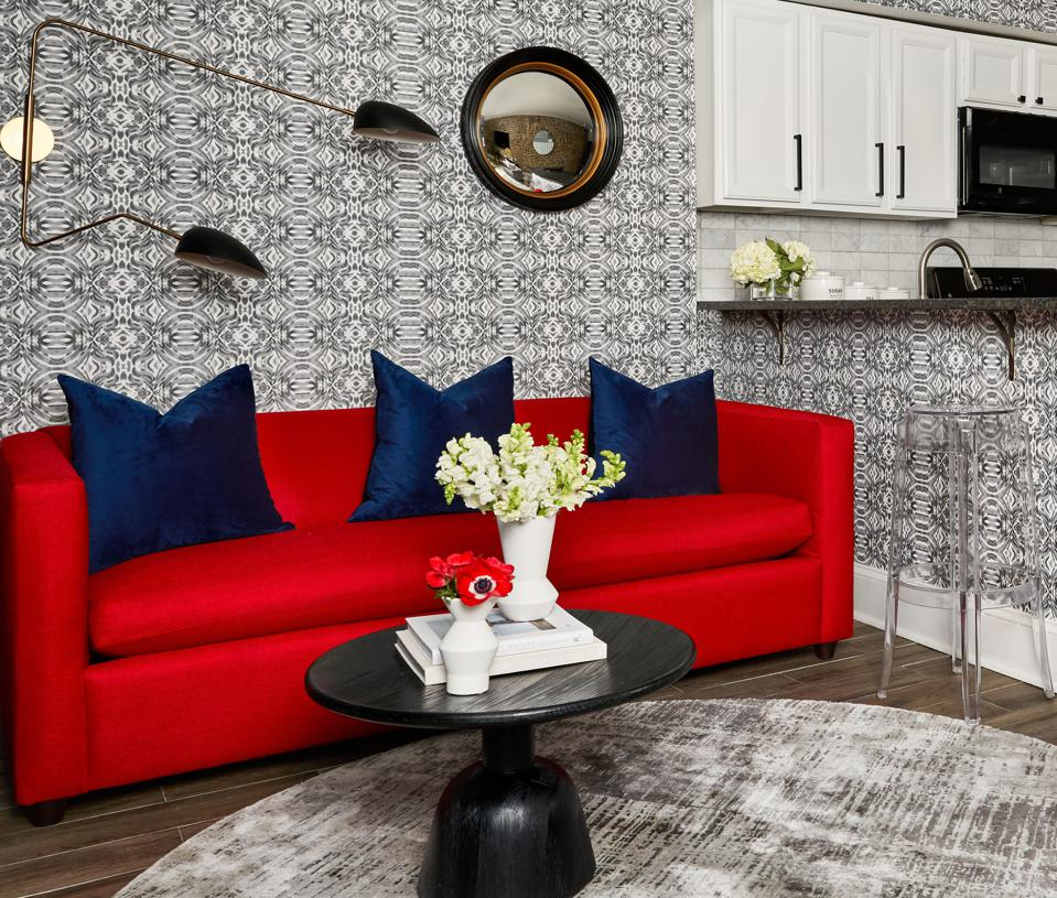 A living room with gray wallpaper and a red sofa.