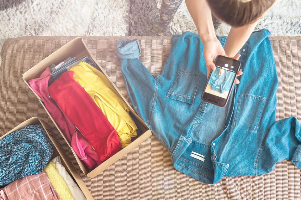 Woman taking photo of denim shirt on smartphone to sell it on internet shop.