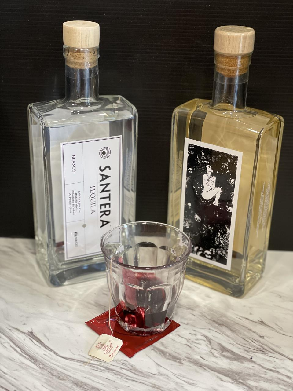 A bottle of Santera Blanco tequila and a bottle of Santera  reposado tequila are in the background of a glass of deep pink-red tequila that has been infused with a hibiscus flower tea bag.