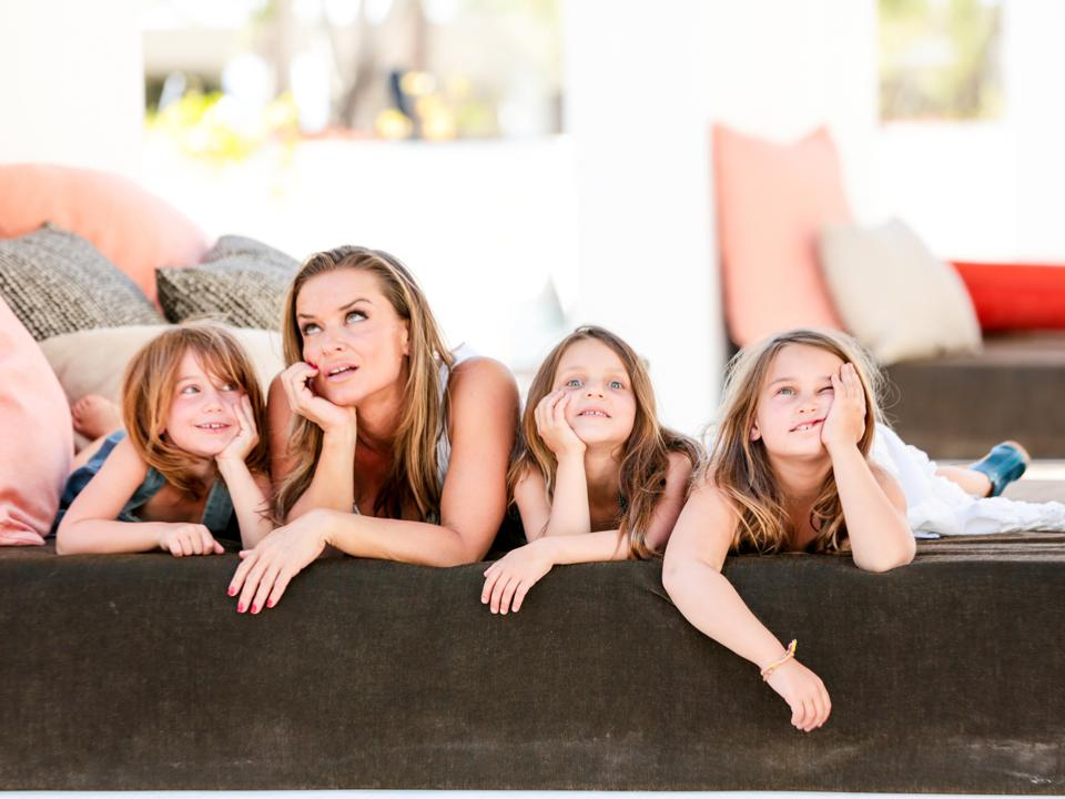 Green and her three girls pose lying down with silly faces.