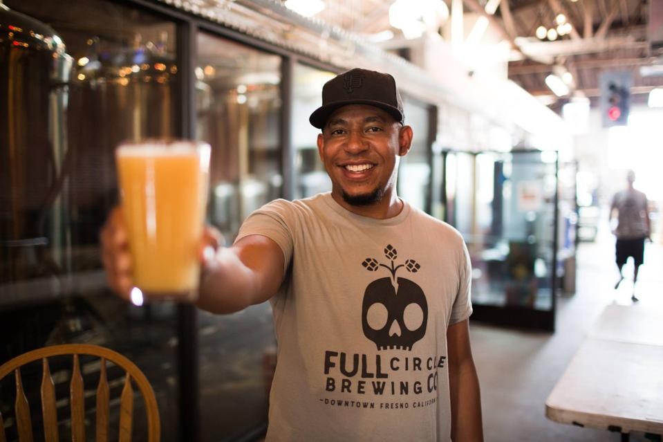 Full Circle Brewing Co. owner Arthur Moye lifts a pint at his brewery in Fresno, California.