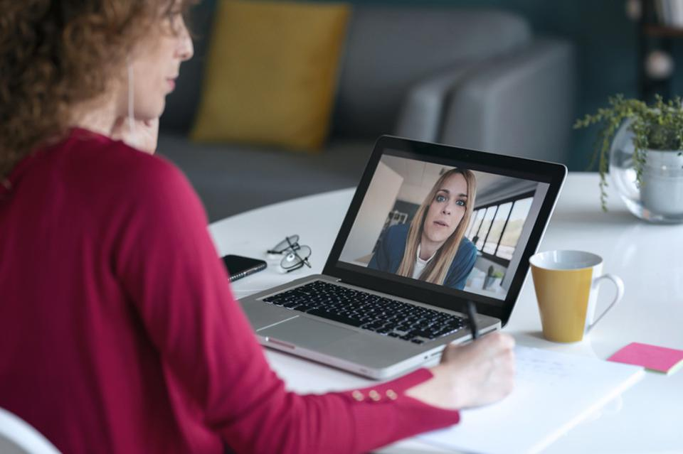 Young female entrepreneur is attending video conference through laptop at home office