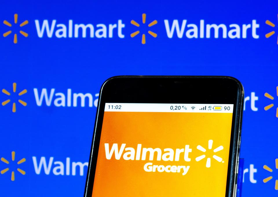 In this photo illustration, a Walmart Online Grocery logo...